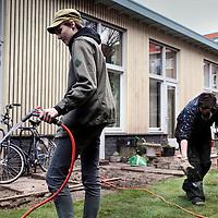 Nederland, Amsterdam , 4 april 2015.<br /> Bewoners van woongroep de Plofhoek (voormalige krakers) leggen een grasmaat aan in hun tuin.<br /> Foto:Jean-Pierre Jans