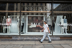 © Licensed to London News Pictures. 14/06/2020. London, UK. A man walks past the Regent Street branch of Reiss . The government has announced that all non-essential retailers can re-open on Monday 15 June as the coronavirus lockdown restrictions are eased . Photo credit: George Cracknell Wright/LNP