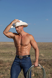 shirtless muscular cowboy on a ranch at sunset