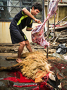 24 SEPTEMBER 2015 - BANGKOK, THAILAND:  A man butchers a sacrificed sheep while a mortally wounded ram bleeds out during the celebration of Eid al-Adha at Haroon Mosque in Bangkok. Eid al-Adha is also called the Feast of Sacrifice, the Greater Eid or Baqar-Eid. It is the second of two religious holidays celebrated by Muslims worldwide each year. It honors the willingness of Abraham to sacrifice his son, as an act of submission to God's command. Goats, sheep and cows are sacrificed in a ritualistic manner after services in the mosque. The meat from the sacrificed animal is supposed to be divided into three parts. The family retains one third of the share; another third is given to relatives, friends and neighbors; and the remaining third is given to the poor and needy.    PHOTO BY JACK KURTZ