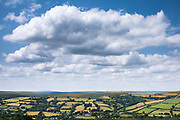 Spectacular far-reaching views over picturesque Dartmoor in Devon with blue sky and puffy clouds in Southern England, UK