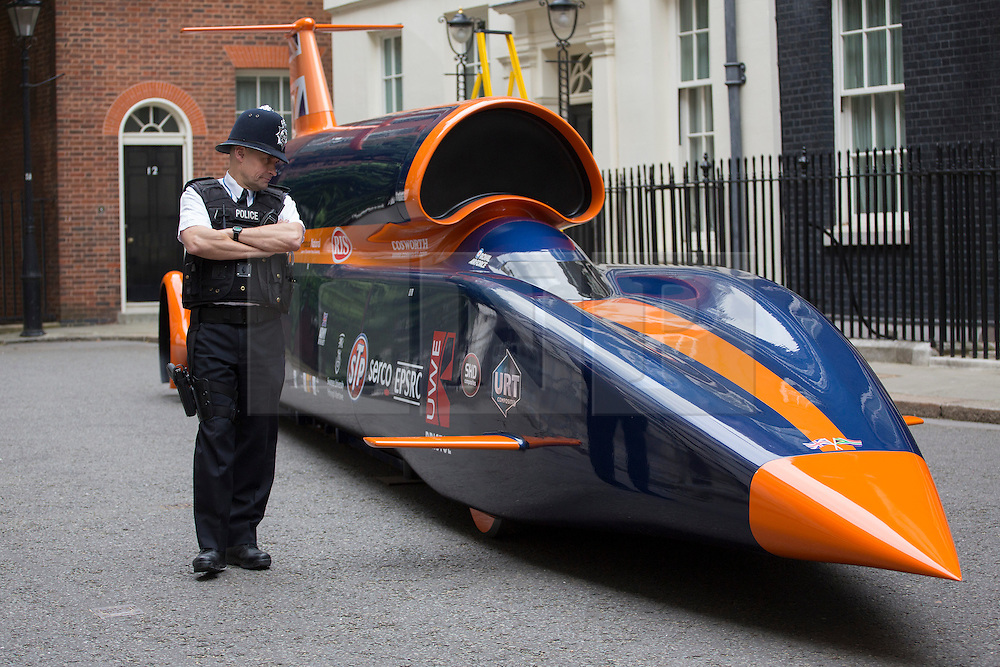 © licensed to London News Pictures. London, UK 24/06/2013. A police officer on Downing Street looking a replica of 13-metre long jet-and-rocket propelled Super Sonic Car which aims to beat the current land speed record of 763mph in 2014 and also to be the first land vehicle to exceed 1,000mph by 2015. Prime Minister is to announce a new apprenticeship initiative to create 100,000 Engineering Technicians. Photo credit: Tolga Akmen/LNP