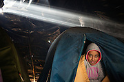 Calais, Januari 2015. Human rights watch reports about the conditions thousands of stranded refugees have to deal with in Calais, on their way to the UK. In camps or 'jungles', several thousand asylum seekers and migrants, people from Syria, Iraq, Eritrea, Ethiopia, Sudan, Pakistan and Afghanistan are living in makeshift camps or in the streets in Calais. Some said that their treatment by police, a lack of housing for asylum seekers, and delays in the French asylum system had deterred them from seeking asylum in France.<br /> <br /> ( better garantee anonimity of this African 20 yr-old woman from Eritrea, who awakes in a smokey tent )