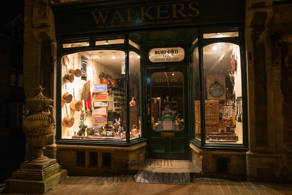 Window display at Walker's stoves and antiques shop along Burford High Street at night, The Cotswolds