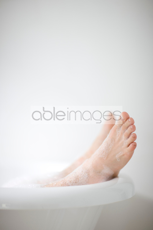 Close up of man feet covered in foam coming out of roll top bath