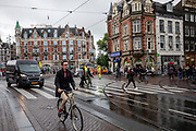 Op het Muntplein in Amsterdam rijdt een fietser door de verkeersdrukte.<br /> <br /> At the Munt square in Amsterdam a cyclist rides at the crowded traffic.