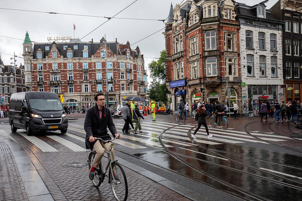Op het Muntplein in Amsterdam rijdt een fietser door de verkeersdrukte.<br /> <br /> At the Munt square in Amsterdam a cyclist rides at the crowded traffic.