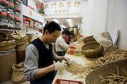 Man prepares Korean Red Ginseng roots for sale at Tai Lai Ginseng Hong shop, Wing Lok Street, Sheung Wan, China