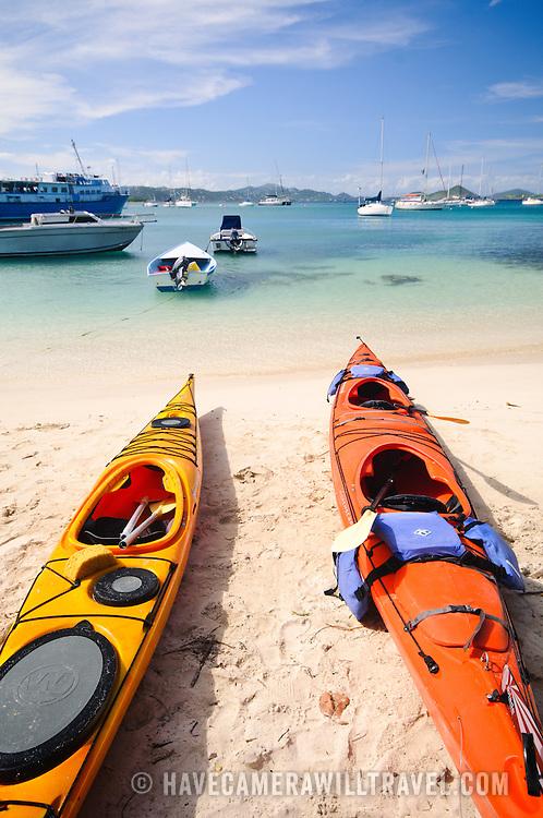 Colorful sea kayaks on the sandy beach at Cruz Bay on St. John in the US Virgin Islands.