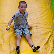 August 16, 2014, New Haven, CT:<br /> A young fan slides down a slide during a tennis clinic in the AETNA FitZone as part of Kids Day on day three of the 2014 Connecticut Open at the Yale University Tennis Center in New Haven, Connecticut Sunday, August 17, 2014.<br /> (Photo by Billie Weiss/Connecticut Open)