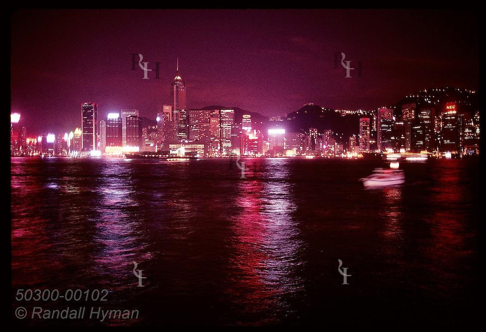 City lights dance across harbor at night as boats pass in blur; view of Hong Kong from Kowloon. Hong Kong