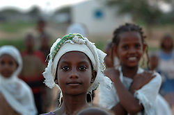 """Young coptic christians pray outside St. Mary's church in the village of Fithi which means """"justice"""" on the outskirts of  Barentu, Eritrea August 27, 2006. During this ceremony, a baby  was baptized with the name Mihreteab. (Photo by Ami Vitale)"""