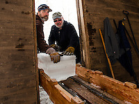 Eric Morse and Bill Sharkey slide ice blocks down the shute into the Rockywold Ice House during the ice harvest with the Rockywold-Deephaven Camp crew on Wednesday. (Karen Bobotas/for the Laconia Daily Sun)