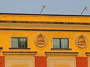 Orange and brown ministry buildings surrounding  Skanderbeg Square are decorated with  the helmet of Gjergj Kastrioti, Skanderbeg. The helmet is topped by a horned goat's head. Skanderberq Square. Tirana, Albania. 02Sep15
