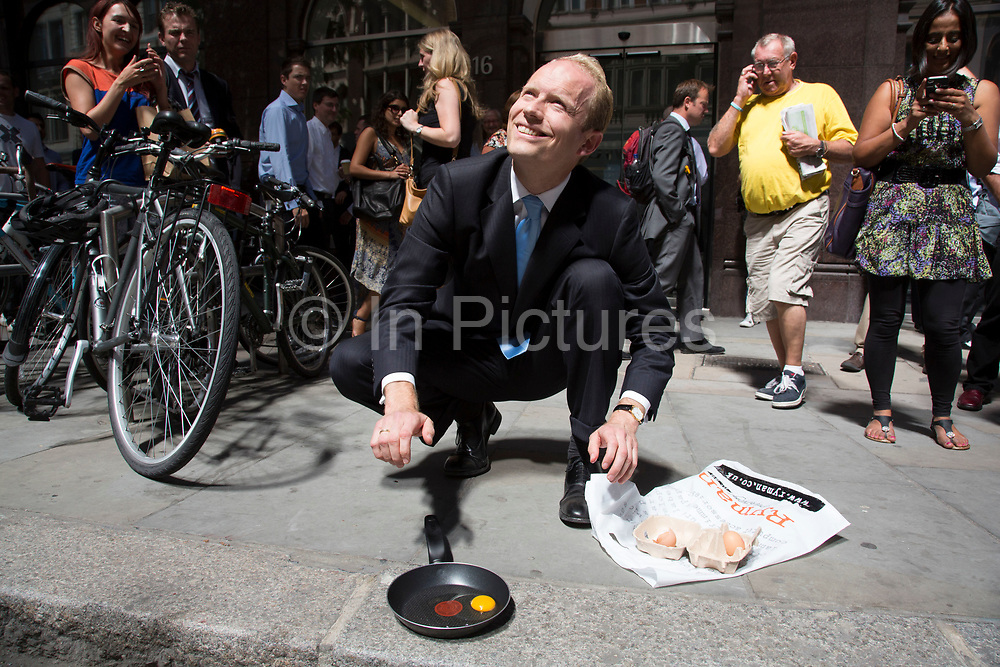 """London, UK. Thursday 5th September 2013. City worker trying to fry an egg during his lunch hour. Urgent action in planned to """"cover up"""" the Walkie Talkie skyscraper in the City after sunlight reflected from the building melted a car on the streets below. Temperatures have been measured in excess of 50 degrees C, and as much as 70 degrees at it's peak. The 525ft building has been renamed the """"Walkie Scorchie"""" after its distinctive concave surfaces reflected a dazzling beam of light which has caused extensive damage to nearby buildings."""