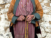 A Brokpa woman wearing her traditional clothing outside the temple on an 'auspicious day' in the remote village of Merak in Eastern Bhutan. The Brokpa, the semi-nomads of the villages of Merak and Sakteng are said to have migrated to Bhutan a few centuries ago from the Tshona region of Southern Tibet. Thriving on rearing yaks and sheep, the Brokpas have maintained many of their unique traditions and customs.