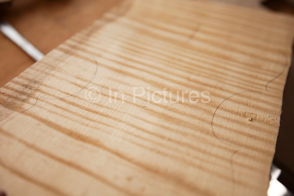 Clear markings of the grain of this spruce wood. Violins being made at viloin an cello maker, Rod Ward's studio in Guilden Morden, Hertfordshire, UK. This highly skilled craft involves the process of making from raw wood to final instrument. All hand crafted with specialist tools and care for detail.