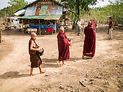 25 MAY 2013 - MAE SOT, TAK, THAILAND: Burmese novices on their morning alms rounds walk past a small shop selling snacks and cigarettes in an unofficial village of Burmese refugees north of Mae Sot, Thailand. They live on a narrow strip of land about 200 meters deep and 400 meters long that juts into Thailand. The land is technically Burma but it is on the Thai side of the Moei River, which marks most of the border in this part of Thailand. The refugees, a mix of Buddhists and Christians, settled on the land years ago to avoid strife in Myanmar (Burma). For all practical purposes they live in Thailand. They shop in Thai markets and see their produce to Thai buyers. About 200 people live in thatched huts spread throughout the community. They're close enough to Mae Sot that some can work in town and Burmese merchants from Mae Sot come out to their village to do business with them.   PHOTO BY JACK KURTZ