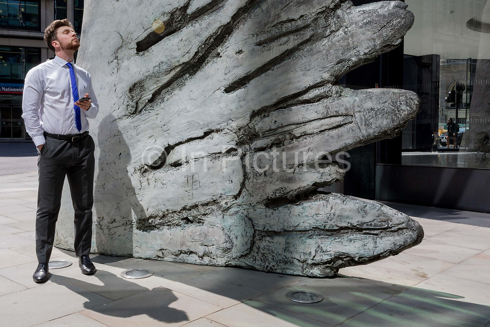 A financial industry businessman stands beneath the sculpture entitled City Wing on Threadneedle Street in the City of London, the capitals financial district aka the Square Mile, on 11th July 2019, in London, England. City Wing is by the artist Christopher Le Brun. The ten-metre-tall bronze sculpture is by President of the Royal Academy of Arts, Christopher Le Brun, commissioned by Hammerson in 2009. It is called 'The City Wing' and has been cast by Morris Singer Art Founders, reputedly the oldest fine art foundry in the world.