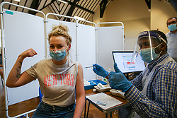 © Licensed to London News Pictures. 17/06/2021. London, UK. Ewa Gruszviewicz and vaccinator Ahmed Said gesture as she receives her first dose of the Pfizer Covid-19 vaccine to at a vaccination centre in Tottenham, north London. <br /> All over-18s in England should be able to book their Covid-19 vaccination from tomorrow. More than 60.5 million doses of coronavirus vaccine have been administered in England, according to NHS England data. Photo credit: Dinendra Haria/LNP