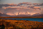 Sunrise on glacier-clad Andes peaks at Lake Argentino, near El Calafate, Santa Cruz Province, Argentina, Patagonia, South America. Lago Argentino is the biggest freshwater lake in Argentina. It has an average depth of 150 m (492 ft), and a maximum depth of 500 m (1,640 ft). The lake lies within Los Glaciares National Park and is fed by glacial meltwater of several rivers, the water from Lake Viedma brought by La Leona River, and many mountain streams. Its waters flow into the Atlantic Ocean through the Santa Cruz River. Los Glaciares National Park is honored on UNESCO's World Heritage List.
