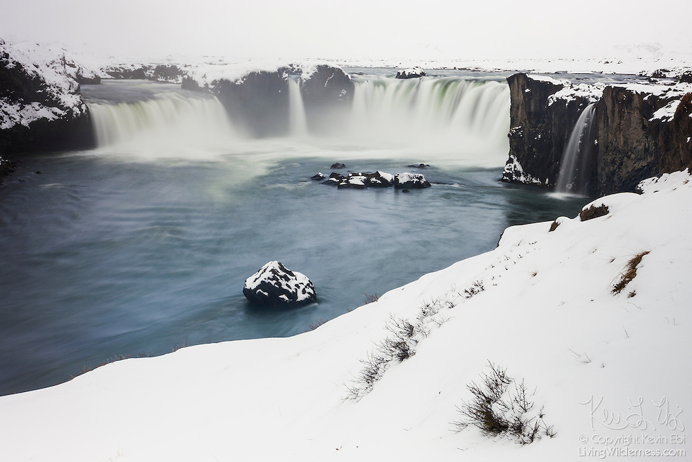 """Heavy snow blankets the banks of Goðafoss, regarded one of the most spectacular waterfalls in Iceland. The name Goðafoss means """"Waterfall of the Gods."""" Located near Mývatn, it plunges 12 meters and is more than 30 meters wide, and is the largest waterfall on the Skjálfandafljót river. The name, however, comes from Icelandic legend: in the year 1000 AD, Þorgeir Ljósvetningagoði, a chieftain in the region, threw his statues of the pagan gods into Goðafoss when he decided Icelanders should adopt Christianity."""
