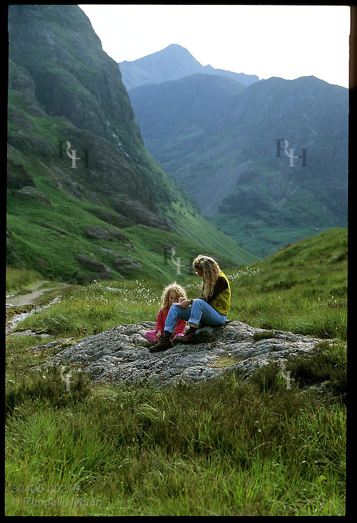 Mom and girl rest on rock along trail in upper Glen Coe on a July afternoon; Glencoe Scotland.