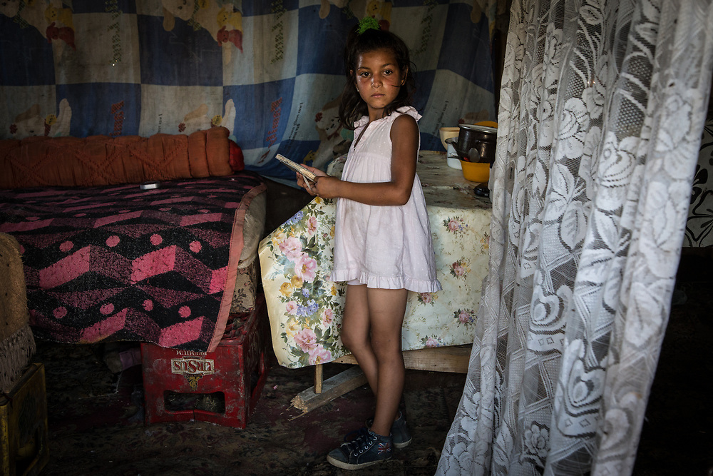 Denisa cleans her house in a slum in the middle of the Pata Rat garbage dump outside Cluj-Napoca, Romania.                                                                                           © Daniel Barreto Mezzano