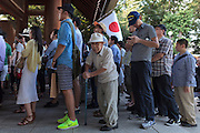 People line up to pray for fallen military servicemen during the 70th anniversary celebrations of the end of the Pacific war  at the controversial Yasukuni Shrine in Kudanshita, Tokyo, Japan Saturday August 15th 2015