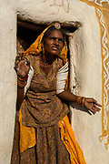 Woman outside of her home. She wears the tradition dress of the area, a skirt, blouse and scarf as well as ankle bracelets and arm bracelets. This upper arm bracelets indicate that she is married and on the death of her husband will be removed and broken. Her home doorway has a 'Dhengan' or ritual painting around the doorway. The home is made from adobe.<br /> Rajasthan, INDIA