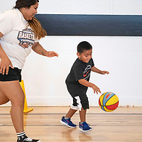 Sherilynn Herrera, a volunteer instructor and St. Michael  graduate plays defense while Lincoln George, 5, dribbles, Thursday morning at St. Michael Indian School summer basketball Cardinal Camp in St. Michaels, Arizona.