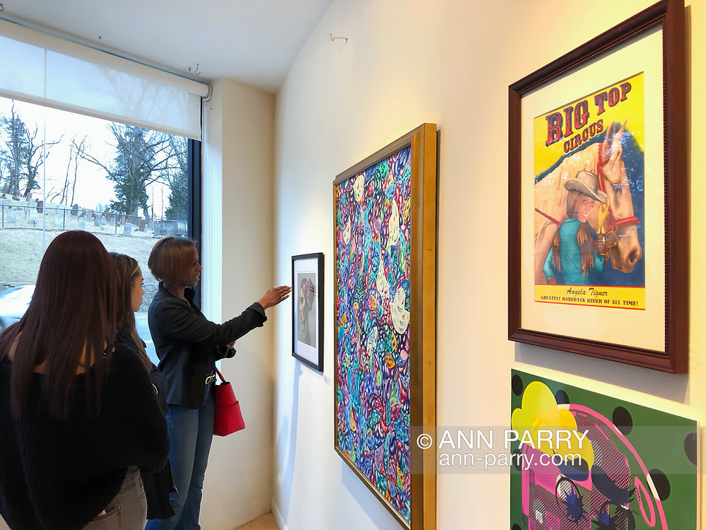 """Huntington, New York, USA. March 29, 2019. Huntington Arts Council Opening Reception for Bright Colors Bold Strokes, Creations of Lowbrow Art, on March 29, 2019. Juror was Stephen Owens. Artist Bob Stuhmer: """"Bareback Rider"""" and """"Polaner"""" - each 16""""x20"""" marker illustrations. Angela Tengler - model for Stuhmer's """"Bareback Rider"""" - attended with her two daughters. Artist Eileen Palmer: """"More-a-Logo"""" 50""""x30"""" collage of fabric, glitter, labels, maps... Artist Ratgrrl (Jessica Valentin) 10""""x20"""" digital collage """"Martian in this World."""" Marc Courtade is Executive Director of HAC."""