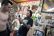 Tattoo artist Joe Adamson, left, makes a photo of the arm of Joey Shaber after completing his work at the Primrose Tattoo parlor, which is located in the area known as the Milk District in Orlando, Fla., Saturday, March 25, 2017. (Phelan M. Ebenhack via AP)