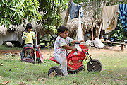 Surui children play with old suitcases and a plastic motorbike<br /><br />An Amazonian tribal chief Almir Narayamogo, leader of 1350 Surui Indians in Rondônia, near Cacaol, Brazil, with a $100,000 bounty on his head, is fighting for the survival of his people and their forest, and using the world's modern hi-tech tools; computers, smartphones, Google Earth and digital forestry surveillance. So far their fight has been very effective, leading to a most promising and novel result. In 2013, Almir Narayamogo, led his people to be the first and unique indigenous tribe in the world to manage their own REDD+ carbon project and sell carbon credits to the industrial world. By marketing the CO2 capacity of 250 000 hectares of their virgin forest, the forty year old Surui, has ensured the preservation, as well as a future of his community. <br /><br />In 2009, the four clans and 25 Surui villages voted in favour of a total moratorium on logging and the carbon credits project. <br /><br />They still face deforestation problems, such as illegal logging, and gold mining which causes pollution of their river systems