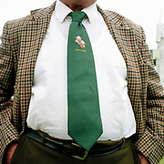 A farmer wearing a green tie with a Hereford cattle motif and a check jacket at the Tenbury Agricultural Show, Worcestershire, UK