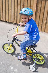 Little boy learning to ride a bike,