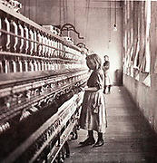 Girl tending a spinning machine, c1900. At this date it was estimated that up to 1,752,000 children under sixteen worked in USA factories.  In the Southern cotton mills one quarter of the 'hands' were children like the one pictured here.