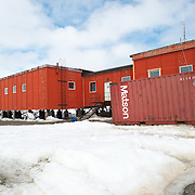 Red prefabricated buildings used for residences and offices at Bellingshausen Station, a Russian scientifc research station in Antarctica.