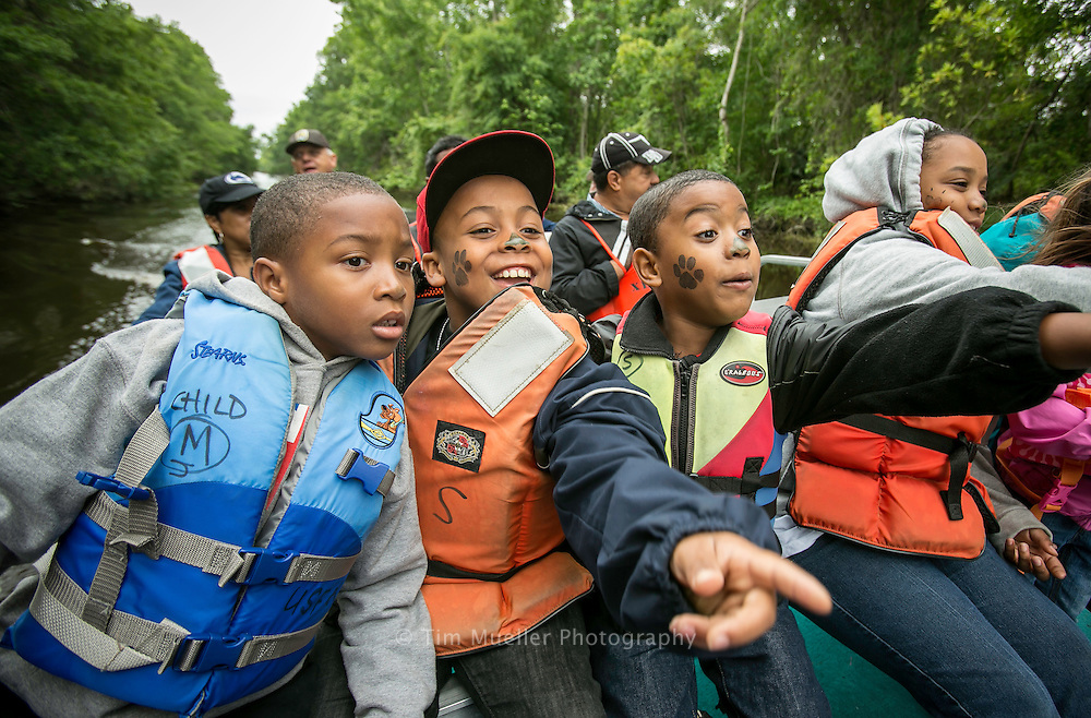 """Franklin, Louisiana residents, from left, Jarion Hill, Donald Hill, Eugene Foulcard, Jr, and A'Myrie Foulcard take a boat trip into the Bayou Teche Wildlife Refuge during the Ninth Annual Bayou Teche Black Bear Festival, April 20-22, 2012, in Franklin, Louisiana. The festival's main goal is to educate the citizens of south Louisiana about the Louisiana black bear, a species listed by the US Fish and Wildlife Service as """"threatened"""" under the guidelines of the Endangered Species Act."""