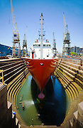 A ship with a red hull receives maintenance while in the dry dock inside the Cape Town Harbour.