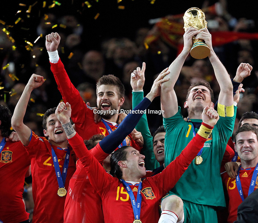 epa02245530 Spain's Iker Casillas (R) hoists the World Cup Trophy after Spain defeated Netherlands 1-0 during the FIFA World Cup 2010 Final match between the Netherlands and Spain at the Soccer City stadium outside Johannesburg, South Africa, 11 July 2010.  EPA/KERIM OKTEN Please refer to www.epa.eu/downloads/FIFA-WorldCup2010-Terms-and-Conditions.pdf