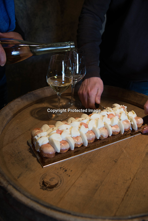 France. Alsace, a bottle of Vendanges tardives  wine and a kiwi cake on a barrel in a cellar