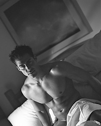 muscular nude man at home in bed covered by bedsheets