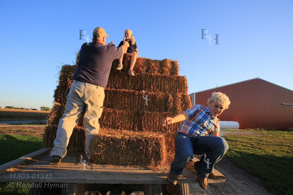 Brad Corzatt helps daughter Mallory off top of hay wagon while her brother Logan jumps down on their farm; Berwick, Illinois.