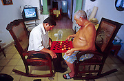 23 JULY 2002 - TRINIDAD, SANCTI SPIRITUS, CUBA: Men play checkers in their home while a baseball game is on the television in the background in the colonial city of Trinidad, province of Sancti Spiritus, Cuba, July 23, 2002. Trinidad is one of the oldest cities in Cuba and was founded in 1514..PHOTO BY JACK KURTZ