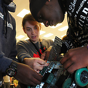 BRUNSWICK, Maine --  12/17/13 --  Portland High Schoolers Daniel, 17, (left) and his brother Benjamin, 18, Semukanya work together with their teacher, Rosalee Lamm to adjust their competition robot at Southern Maine Community College (SMCC) last Tuesday. High School Students from Portland, Lewiston and Kennebunk gathered at SMCC's Brunswick center for their first robotics competition. A Bank of America grant to Portland and Lewiston started them up last spring -- giving an opportunity for young adults to work in teams to conceive, build, program and operate the small robots.  Photo © Roger S. Duncan 2013.