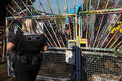 London, UK. 26th February, 2019. A bailiff outside the entrance to Grow Heathrow, a squatted eco-community founded in 2010 on a previously derelict site close to Heathrow airport in protest against government plans for a third runway. Bailiffs from the National Eviction Team today evicted residents from the front section of the site owned by Imran Malik, removing several protesters locked on in towers above the camp, but four protesters are believed to remain in a tunnel beneath that area. Many more protesters remain on the rear portion of the site. Five legal challenges to the government's approval of a 3rd runway at Heathrow will proceed to judicial review at the Royal Courts of Justice on 10th March.