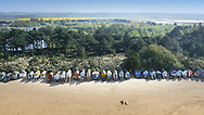 Aerial view of Holkham beach and the colourful huts lining the shore.