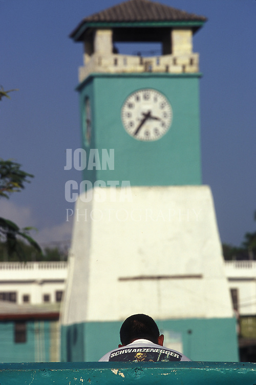 BELIZE / Punta Gorda / Young man with a shirt of Schwarzenegger sitting next to the Clock Tower...© JOAN COSTA