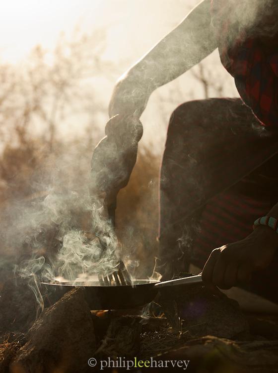 Maasai tribesman cooking over fire for eco tourism camp, Chyulu Hills National Park, Kenya